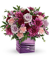 Turn up the glam this Mother's Day with this magnificent mirrored cube, bursting with a lush bouquet of lavender roses and purple mums!  Its silky finish and peaceful waves are sure to enthrall her.  Light pink miniature carnations, burgundy cushion spray chrysanthemums, purple cushion spray chrysanthemums and lavender sinuata statice are arranged with huckleberry and parvifolia eucalyptus.