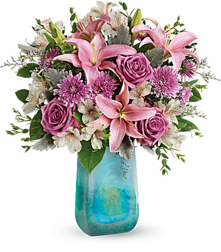 The art of affection! Take her breath away with this beautiful bouquet of lush lavender roses and pink lilies, carefully arranged in a high-fashion, hand-blown art glass vase with swirling iridescent finish.  This bouquet features lavender roses, pink asiatic lilies, light pink alstroemeria, lavender cushion spray chrysanthemums, lavender limonium, dusty miller, parvifolia eucalyptus, and lemon leaf.