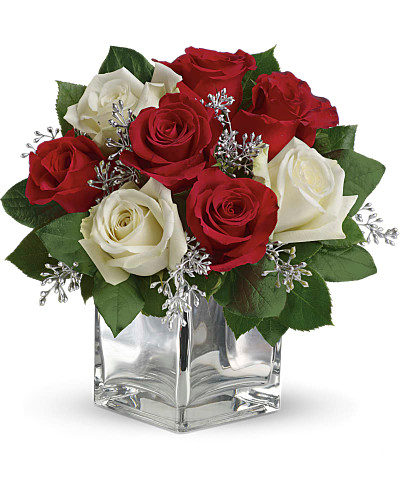 Give Christmas a charmingly contemporary spin with lush red and white roses in a dazzling glass cube. With a merrily moderate price tag, it makes the perfect gift for all the people on your list - naughty or nice.  The impressive bouquet includes red roses and white roses accented with assorted greenery.