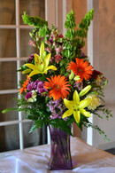 Two thumbs up for mom, a cheerful bright bouquet, filled with vibrant yellow lilies, green bells of Ireland, Orange gerber daisies, purple poms, lavender wax flower put together in a purple square tall vase