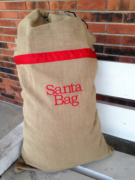 """This burlap Santa bag is perfect for gift giving or used as Christmas décor in your home. It has a black draw sting closure on top and measures 21""""W x 36""""H."""