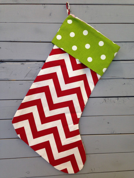 This red and white chevron stocking has a green and white polka dot band on top and a loop for easy decorating. Monogram it to add a personal touch! Monogramming will be placed at the top of the stocking.