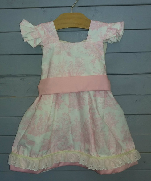 This beautiful dress has so much detail and art work added into the fabric. The waistband really brings it all together. At the bottom of the dress, there is pink fabric to match the waistband. This dress is just too adorable.