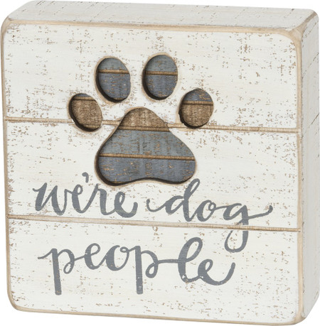 """A slatted wooden box sign lending a """"We're Dog People"""" hand lettered sentiment and a cut-out paw print design with inset striped coloration accents. Easy to hang or can free-stand alone.  Complements well with coordinating design pieces for a great gift set or rustic décor collection. Size:  5"""" x 5"""" x 1.75"""""""