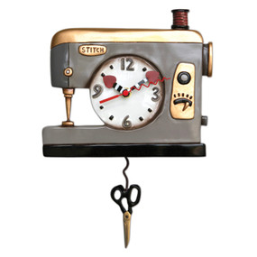"Michelle loves the imperfect, slightly eccentric, witty quality of the world around her.  Her hope is that her art will never become so serious that she betrays the uniqueness of the life that inspires her. Often if something seems too perfect in her art, she will skew it towards the unrealistic to capture the essence of a whim. This sweet sewing machine clock makes a great gift for a seamstress or crafter. Hang it anywhere you just want to add a little bit of vintage vibe. This whimsical clock features:  •    measures 9″ x 12″ •    hand-painted heart hands •    swinging scissors pendulum •    cast in resin, finished by hand •    requires ""AA"" battery"
