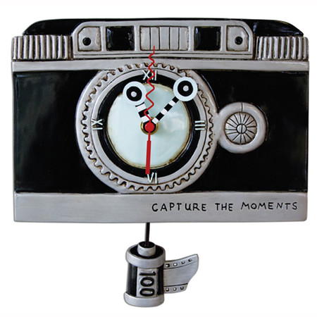 "Vintage camera clock. This whimsical vintage clock features: •    measures 9″x8.5″ •    ""capture the moments"" imprinted on clock •    hand-painted clock hands •    swinging film canister pendulum •    cast in resin, finished by hand"