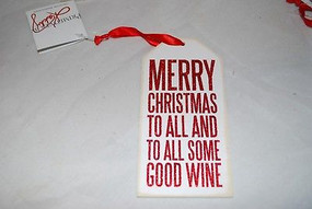 """A red and white wooden bottle tag featuring a humorous """"Merry Christmas To All And To All Some Good Wine"""" sentiment, glitter details, reverse zigzag designs, and top fabric loop for attaching to a bottle of wine."""