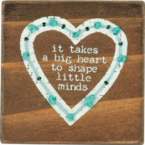 "Square wooden block featuring ""It Takes A Big Heart To Shape Little Minds"" sentiment with a heart design and hand-stitched string details. Contains strong back magnet or can free-stand alone."