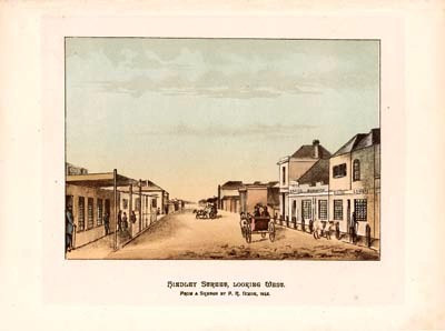 These original chromolithograph was published by E.S.Wigg & Son in 1886. This firm is still with us in 2001, our Federation centenary West alng  Hindley Street in the direction of the Port Adelaide.  The Colony took some time to develop its architecture where pise and mud structures and timber buildings prevailed until the wealth of the 1840's Copper discoveries started to impact on the character of the inner city development. Many Scottish pre fabricated buildings brought out for shelter by the first immigrants, still populated this view.