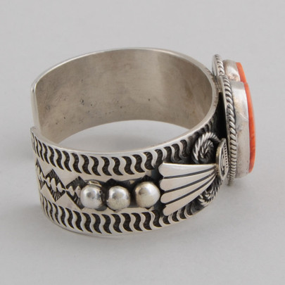 """Tradition stamp work and repousse with wings and """"rope"""" accent a beautiful Orange Spiny Oyster Shell Heart in this Sterling Silver cuff bracelet."""