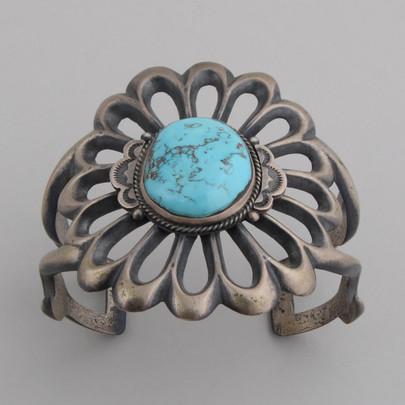 A beautiful sandcast cuff bracelet surrounds a wonderful Kingman Turquoise stone by Harrison Bitsui.