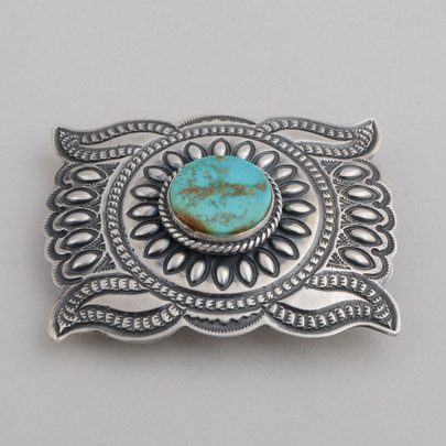 Traditional style buckle with stamp work and repuosse work and a very Kingman Turquoise stone.