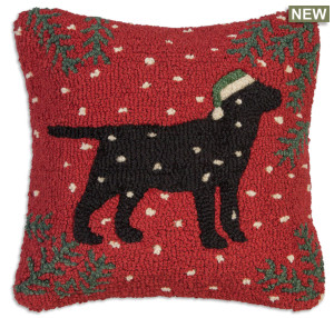 """18"""" square hand hooked pillow, made with 100% natural wool. Zippered velveteen backing with poly-fill pillow insert. Designed by Laura Megroz.  Lab lovers and Christmas lovers can unite in a gorgeous hooked wool holiday pillow! A handsome black Labrador retriever in Christmas stocking cap looks grand against red background with pine boughs in corners and snowflakes drifting down."""