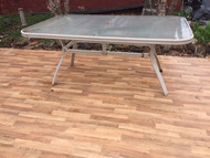 Tan glass top patio table