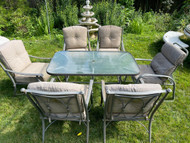 Gray glass top patio table and six chairs with cushions
