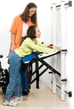 User is wheeled to Support Station, grabs the handholds, and lifts (is lifted) to standing position. When kneeboard is in place (shown in picture), a rolling commode can be moved in. When kneeboard is not used, the Support Station can be pivoted to a standing toilet. Or the client can be diapered with greater ease and better hygiene.