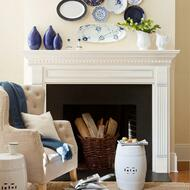 A white wood mantel with dentil molding and fluted legs, for design inspiration