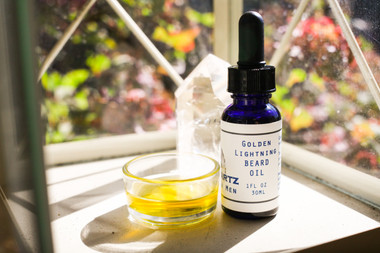 Golden Lightening Beard Oil -  moisturizes dry skin facial hair with energy akin to lightening. Moisturizing camellia oil and jojoba oil are quickly absorbed into the beard, making it soft and healthy. Karanja oil is added to help treat the skin under the beard, preventing any dryness, flakiness,