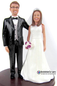 Custom sculpted wedding cake toppers that look like the bride and groom
