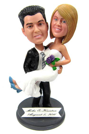 Groom carrying his bride custom wedding cake topper