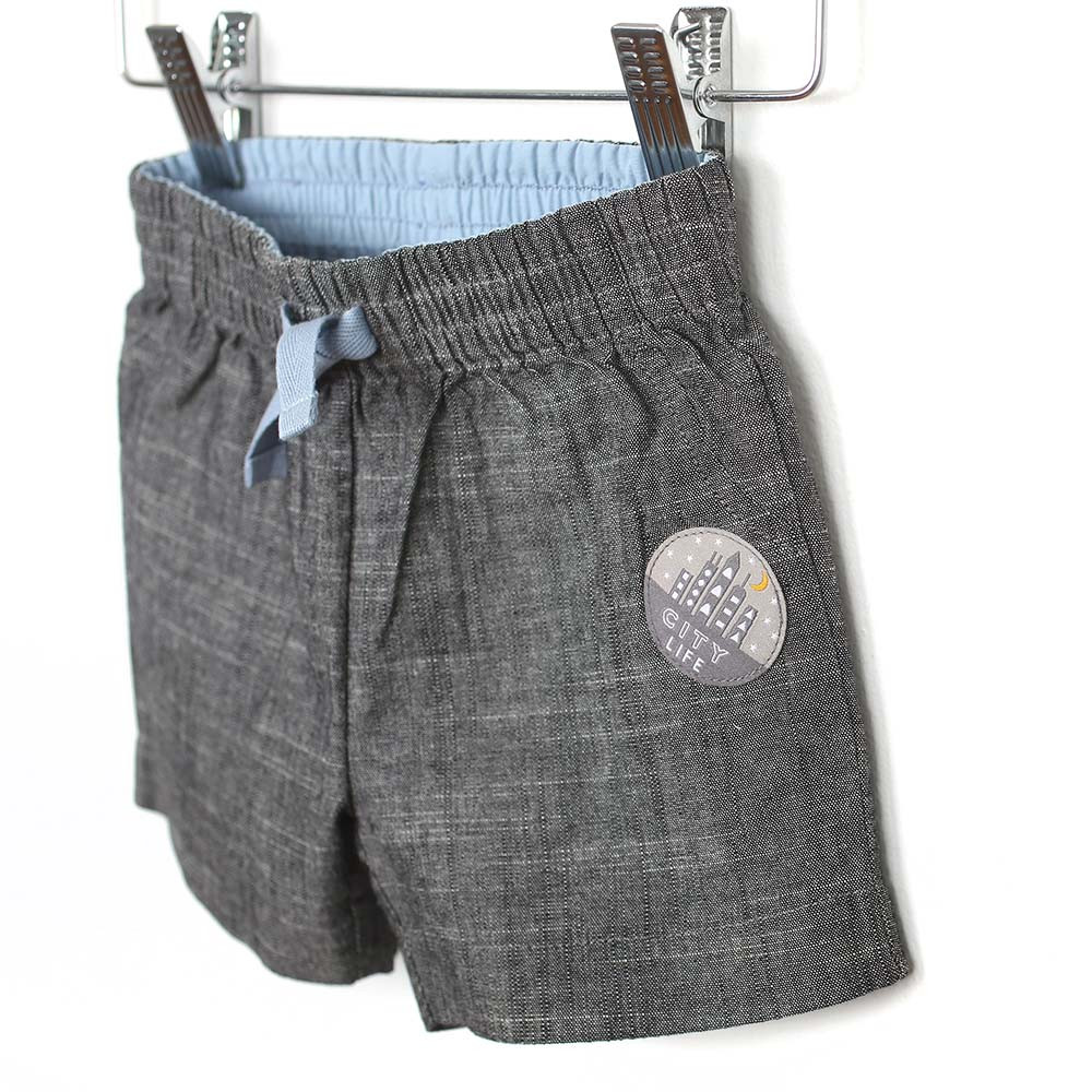 Grey woven shorts with elastic waste and faux drawstring for baby and toddler boys. Side view.