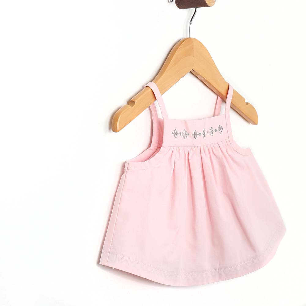 Side view of baby and toddler girl top in pink cotton.