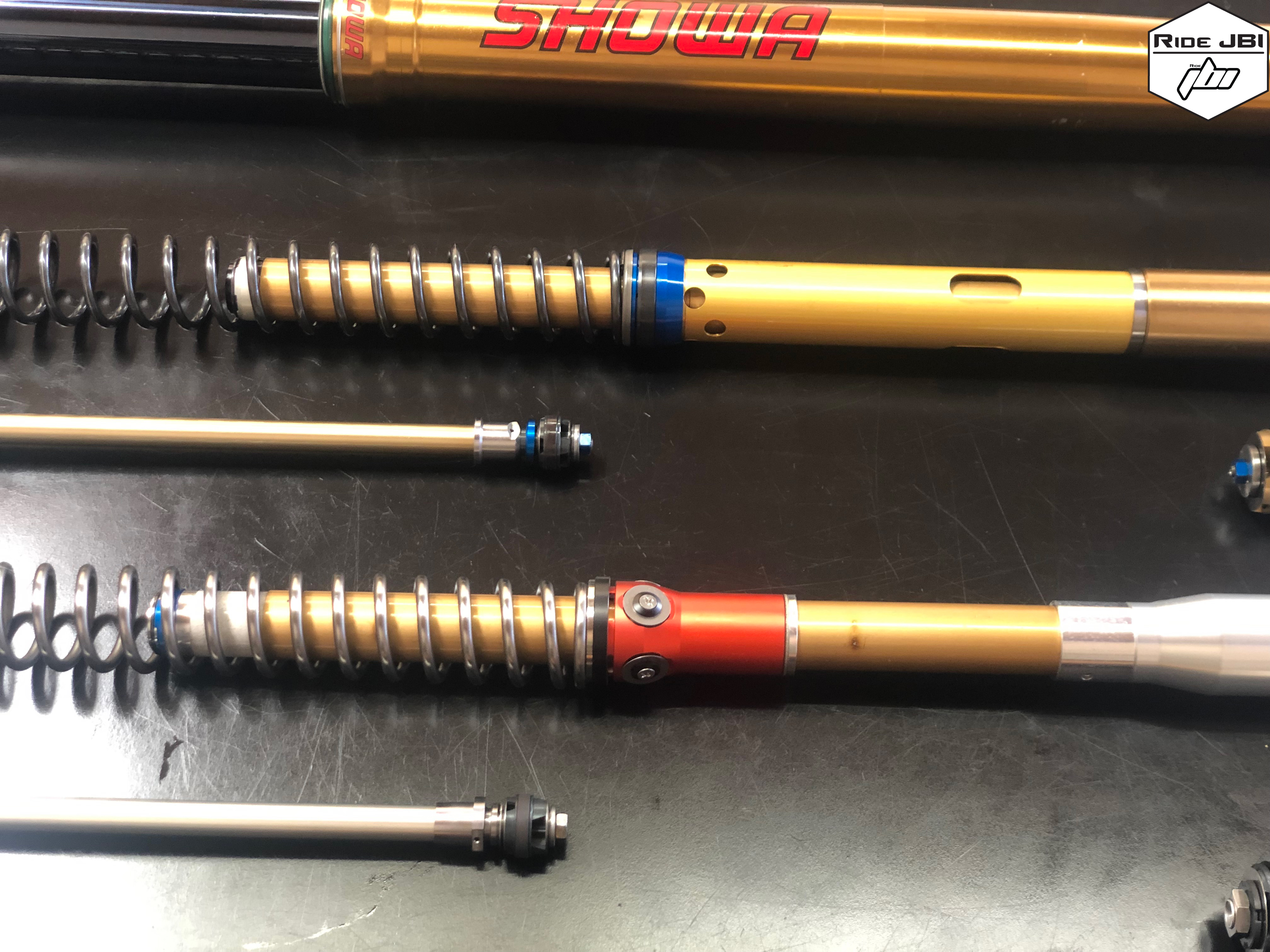 Showa A Kit 49mm Spring Fork next to Showa OEM 49mm Spring Fork