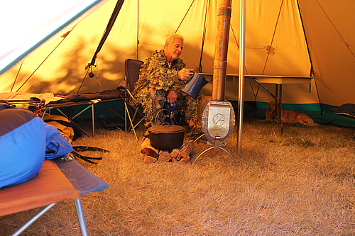 Hunter inside tent enjoying tent stove