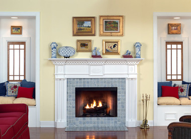 A fireplace mantel with formal traditional colonial styling.  A mantle with columns.