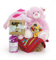 Gift basket for new baby and mom, featuring pink clothing, pink blanket, pink teddy bear, waterproof toys, and a small spa set.