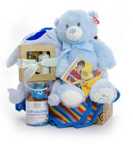 Gift basket for new baby and mom, featuring blue clothing, blue blanket, blue teddy bear, waterproof toys, and a small spa set.