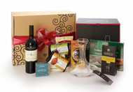 Gourmet gift basket featuring Mission Hill cabernet sauvignon, BC local snacks (chocolate, crackers, smoked salmon, etc.), Riedel wine carafe and Riedel stemware, packaged in signature Green & Green gift box with red ribbon and bow.