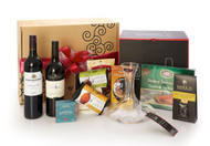 Gourmet gift basket featuring Pirramimma shiraz, Mission Hill cabernet sauvignon, BC local snacks (chocolate, crackers, smoked salmon, etc.), Riedel wine carafe and Riedel stemware, packaged in signature Green & Green gift box with red ribbon and bow.