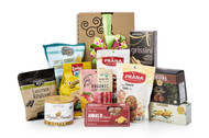 Gourmet gift basket featuring the best international dessert items (chocolate, candies, crackers, etc.), packaged in signature Green & Green gift box with green and polka dot ribbon and bow.