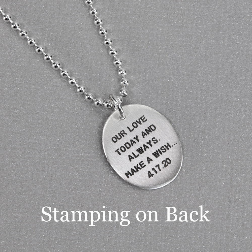 Optional hand stamping on back of Silver Wish Dandelion Necklace, shown on gray background