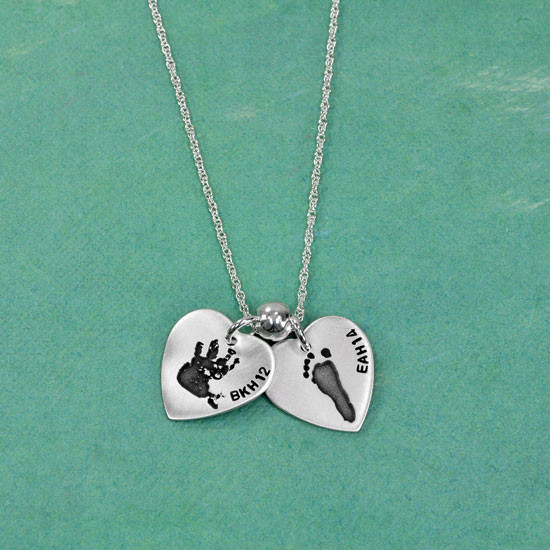 actual handprint & footprint on a silver necklace on a green background