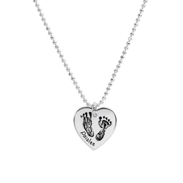 actual footprints on a silver heart necklace on a white background