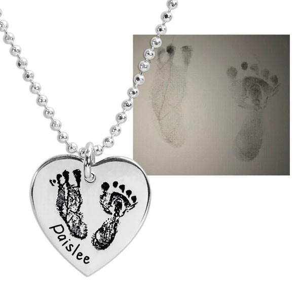 close up of actual footprints on a silver heart necklace on a white background, shown with the original footprints