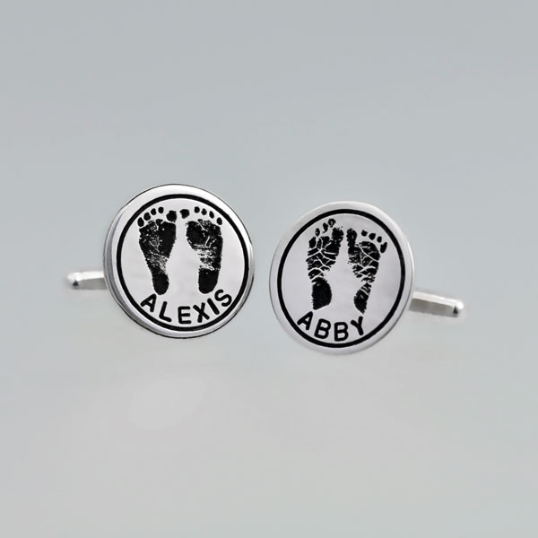 Sterling silver personalized cuff links with your kid's hand prints or footprints, shown on a gray background, with Alexis and Abby names hand stamped on them