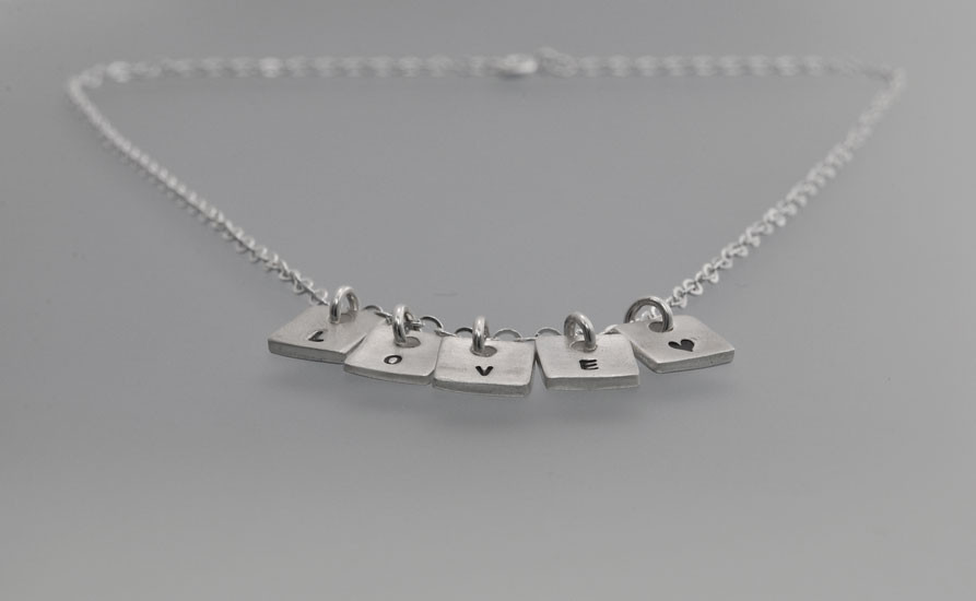 Side view of sterling silver initials necklace tiny squares