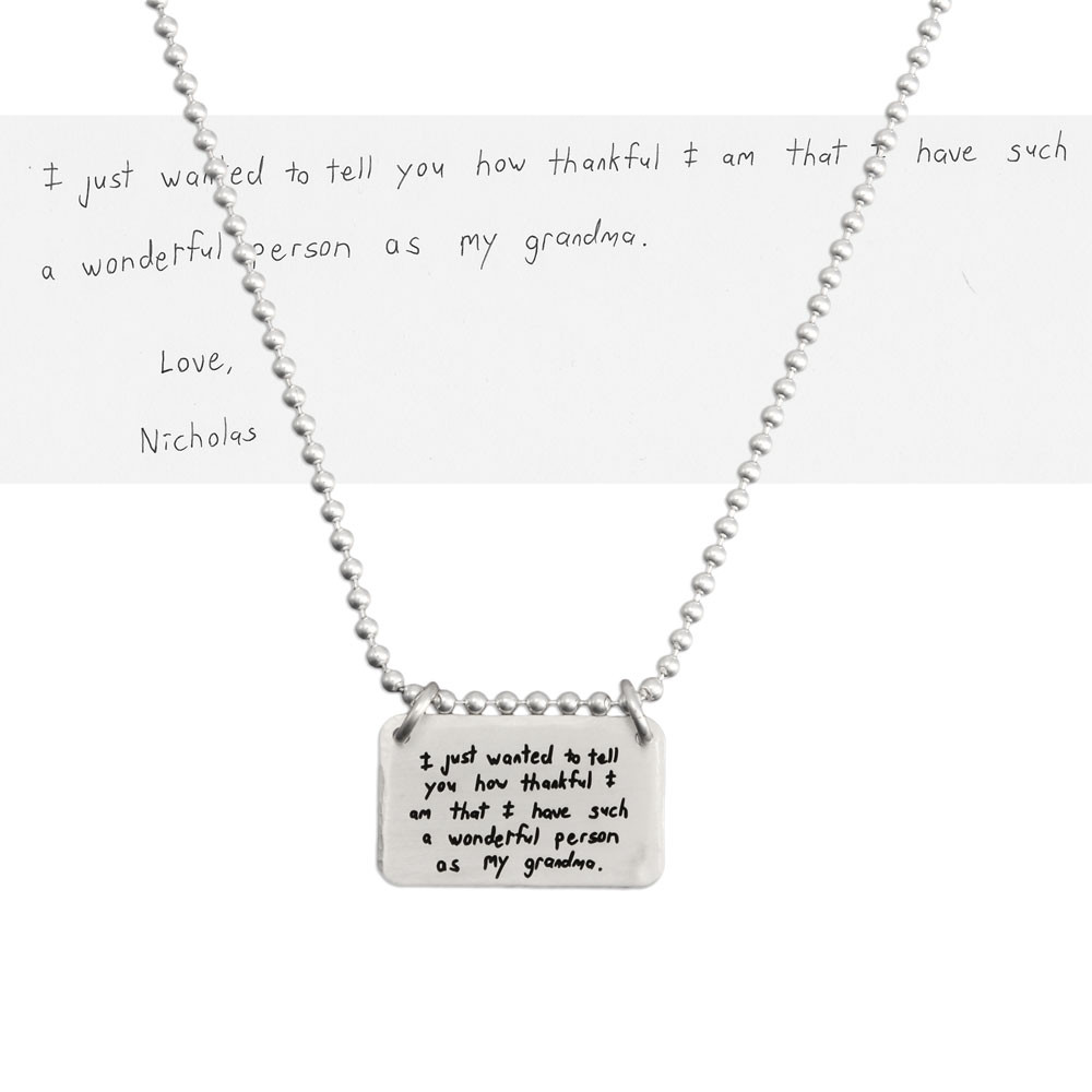 Sterling silver rectangle jewelry made from handwriting, with handwritten note for grandma, shown on white