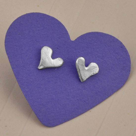 """Loved"" fine silver heart earrings, shown with purple background"