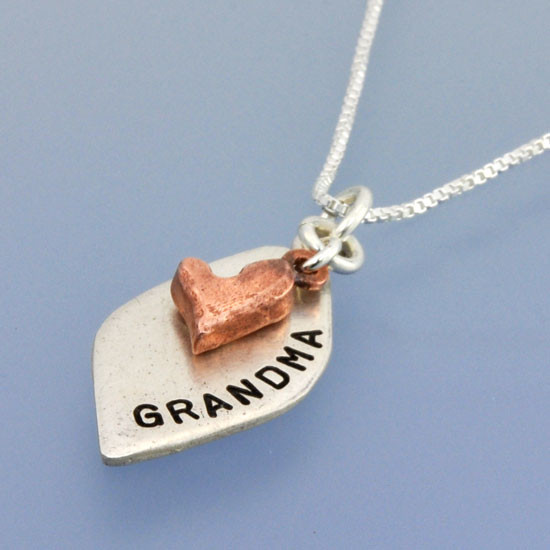 Close up of Hand Stamped Loved Petal Necklace, in fine silver and copper, shown from the side