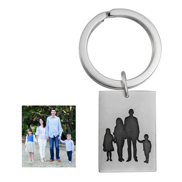 Silhouette of a family photo, etched on a on a silver key ring, shown on white, with original photo used to create it