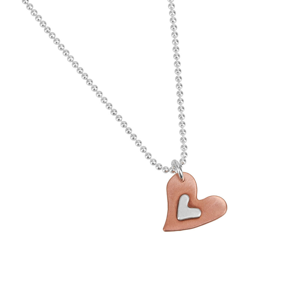 Handmade Subtle Devotion necklace with copper heart and silver heart in the middle, shown on white