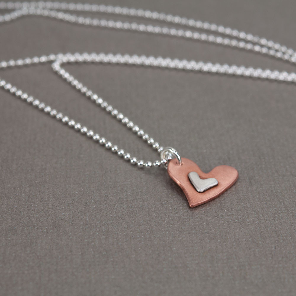 Handmade Subtle Devotion necklace with copper heart and silver heart in the middle, shown from the side