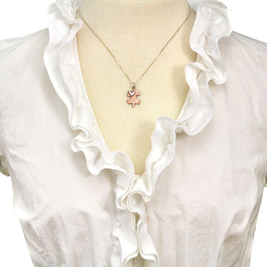 Handmade copper puzzle piece charm with silver heart on a necklace, shown on a model