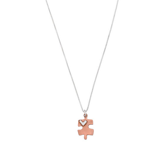 Handmade copper puzzle piece charm with silver heart on a necklace, shown on white