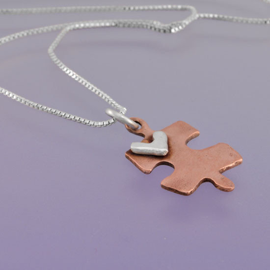 Handmade copper puzzle piece charm with silver heart on a necklace, shown from the side