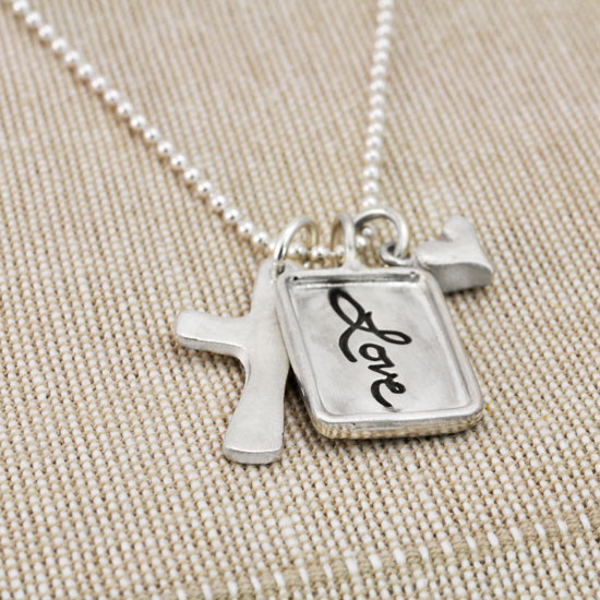 Silver charm with raised edge & the handwritten word Love, with a fine silver cross and fine silver heart, shown from the side